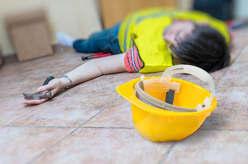 Work injury concept. Worker had an accident and is lying injured on the floor.